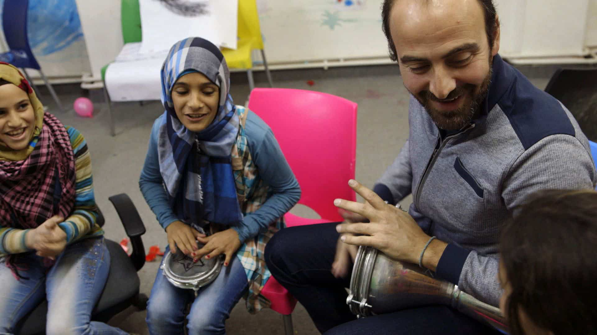 Kinan Azmeh making music with students at a refugee camp in Jordan.