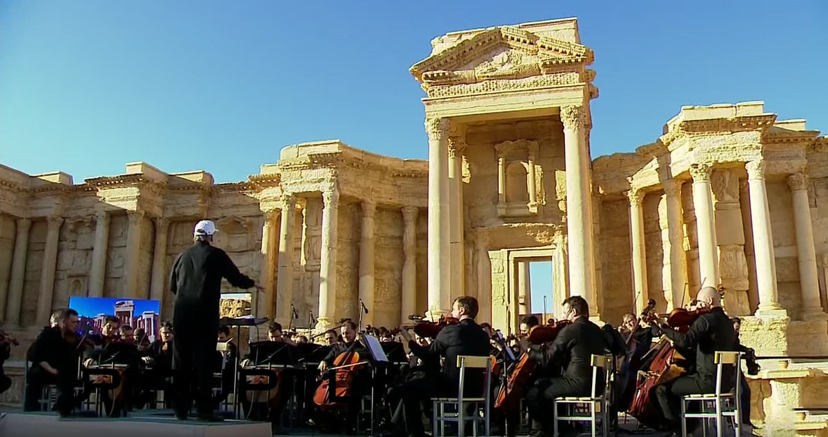 Valery Gergiev leads the Mariinsky Orchestra in a concert for Russian troops among the ruins ofPalmyra, Syria.